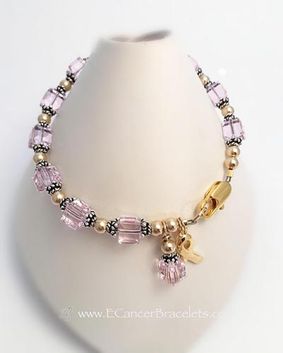 This is a Pink Ribbon Breast Cancer Bracelet. A Gold Ribbon Charm and Crystal Dangle are included in the price. Shown with a Gold Lobster Claw Clasp.